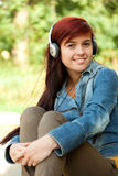 Girl listening to music with headphones Stock Images