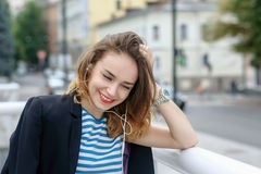 Girl listening to music on headphones and laughs Stock Photos