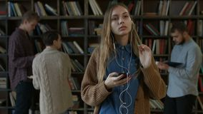 Girl listening to music with headphones in library stock footage