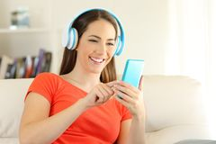 Girl listening to music with headphones and phone at home. Portrait of a happy girl listening to music with headphones and phone sitting on a couch in the living Stock Photo
