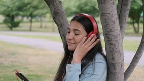 Girl listening to music in headphones sitting near a tree in the park. Close-up. Happy girl with dark hair and jeans clothes is listening to music with stock video