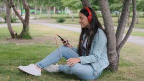 Girl listening to music in headphones sitting near a tree in the park. Happy girl with dark hair and jeans clothes is listening to music with headphones while stock video