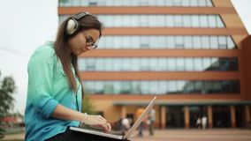 Girl listening to music on headphones and typing on a laptop keyboard. stock footage