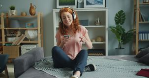Girl listening to music through headphones using smartphone dancing at home. Joyful girl is listening to music through headphones and using smartphone dancing stock video footage