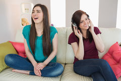 Girl listening to music with her friend beside her on the sofa Royalty Free Stock Photo