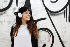 Girl listening to Music while leaning on a Wall Stock Image
