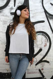 Girl listening to Music while leaning on a Wall Stock Images
