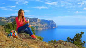 Girl listening to music on the mountain coast Stock Image