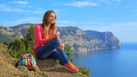 Girl listening to music on the mountain coast Royalty Free Stock Image