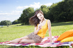 Girl listening to the music in the park Stock Photography