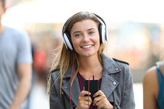 Girl listening to music on phone and looking at you. Front view portrait of a happy girl listening to music on phone and looking at you on the street Stock Images