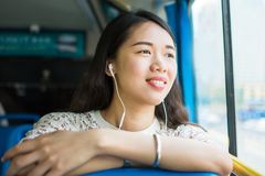Girl listening to music on a public bus Stock Images
