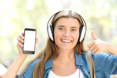 Girl listening to music showing blank phone screen. Front view portrait of a happy girl listening to music showing blank smart phone screen in the street Royalty Free Stock Photo