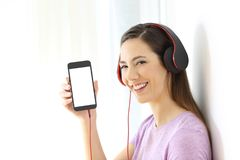 Girl listening to music and showing phone screen. Happy girl listening to music and showing a blank smart phone screen mockup with an isolated background at side Stock Image