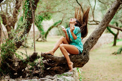 Girl listening to music and sing emotional and drive on smartpho. Long hair girl listening to music emotional and drive on smartphone mobile in green park forest Royalty Free Stock Photos