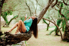 Girl listening to music and sing emotional and drive on smartpho. Long hair girl listening to music emotional and drive on smartphone mobile in green park forest Royalty Free Stock Photo