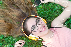 Girl listening to music streaming with headphones in summer on a Stock Images