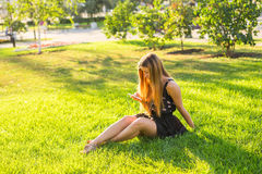 Girl listening to music streaming with headphones in summer on a meadow. Royalty Free Stock Photos