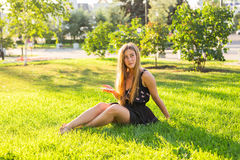 Girl listening to music streaming with headphones in summer on a meadow. Stock Photos