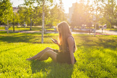 Girl listening to music streaming with headphones in summer on a meadow. Stock Photography