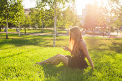 Girl listening to music streaming with headphones in summer on a meadow. Stock Images