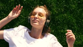Girl listening to music streaming with headphones in summer on a meadow. Green grass. Smiling girl in yellow sunglasses stock footage
