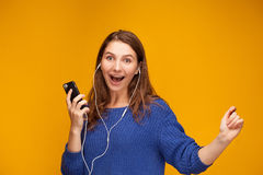 Girl is listening to music. From telephone. She use earphones. She is yong and funny Royalty Free Stock Photo