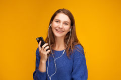 Girl is listening to music. From telephone. She use earphones. She is yong and funny Stock Images