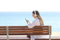 Girl listening to music using phone on the beach royalty free stock images