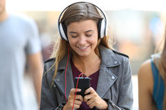 Girl listening to music and walking on the street Stock Photo