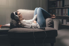 Girl listening to music. Young woman with headphones relaxing at home late at night, she is lying on the armchair and listening to music using a tablet Stock Photography