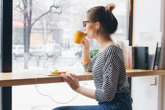 Girl listening to music on your smartphone and drinking coffee. Young beautiful girl listening to music on your smartphone with headphones and drinking coffee Royalty Free Stock Image