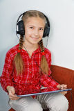 Girl listening to music on your Tablet PC Stock Images
