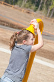 Girl listening to playground phone Stock Photography