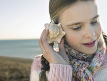 Girl Listening To Seashell On Beach Royalty Free Stock Image
