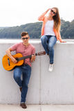Girl listening to serenade. Love romance music talent passion dating concept. Girl listening to serenade. Young boy playing guitar to his lady Royalty Free Stock Photography
