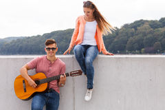 Girl listening to serenade. Love romance music talent passion dating concept. Girl listening to serenade. Young boy playing guitar to his lady Stock Image