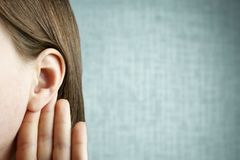 The girl listens attentively with her palm to her ear, close-up, indoors, the news concept royalty free stock photo