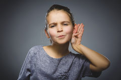 Girl listens. child hearing something, hand to ear gesture on grey background. Curious Disappointed girl listens. Closeup portrait child hearing something Stock Images