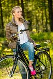 Girl listens music on a bicycle outdoors Stock Photos