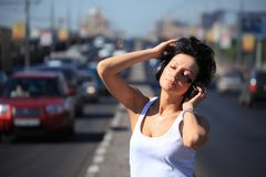 Girl listens music in ear-phones on highway middle Royalty Free Stock Images