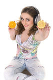 Girl listens music and eats orange Stock Photo