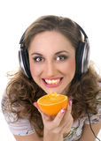 Girl listens music and eats orange Stock Photos
