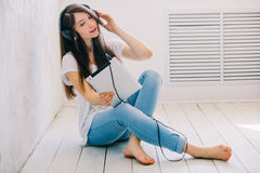 Girl listens music sitting on the floor in the Studio. While cro. Ss-legged. Great tunes Stock Photos