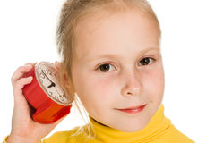 Girl listens ticking of the clock Royalty Free Stock Image
