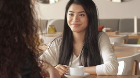 Girl listens to her friend at the cafe. Pretty asian girl listening to her female friend at the cafe. Curly brown haired woman gestures by her hands. Close up of stock video