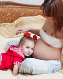 A girl listens to the mother's abdomen Stock Images