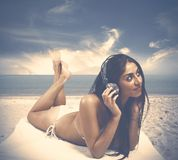Girl listens to music at the beach Stock Photography