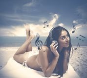 Girl listens to music at the beach Royalty Free Stock Photo