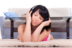 Girl listens to music through ear-phones Stock Image